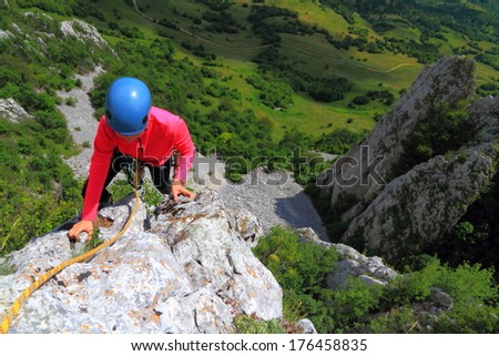 Daring climber grips a hold on aerial rock ridge - stock photo