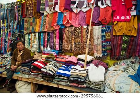 DARJEELING, INDIA - APRIL 14: Tibetan woman sells colorful hand woven woolen garments at Darjeeling Mall Chowrasta market on April 14, 2014 in Darjeeling, West Bengal, India. - stock photo