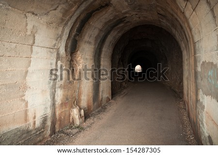 Dark abandoned tunnel interior with glowing end. Petrovac town, Montenegro - stock photo