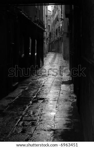 Dark alley in the rainy streets of Venice, Italy. - stock photo