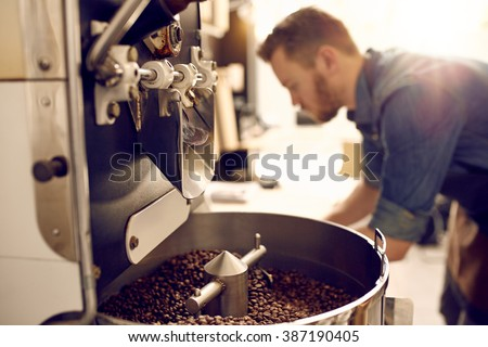Dark and aromatic coffee beans in a modern roasting machine with the blurred image of the professional coffee roaster visible in the background - stock photo
