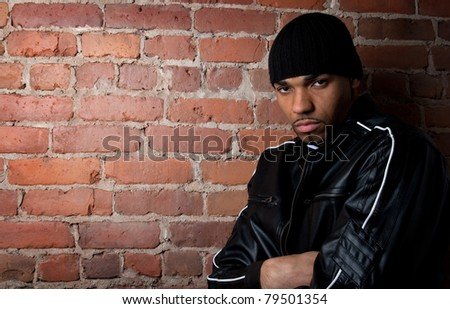 Dark and gloomy guy dressed in black, leaning against the brick wall. - stock photo