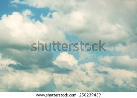 Dark and light clouds in a blue sky, with a vintage feel to it. - stock photo