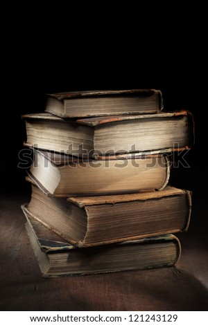 Dark and moody still life with worn and tattered old books. - stock photo