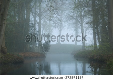 Dark and mysterious mood at a pond in a landscape park on a foggy, spring day. - stock photo