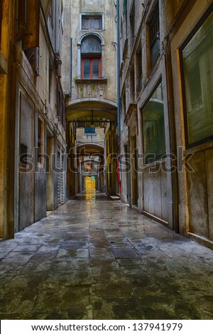 Dark and narrow street in Venice - stock photo