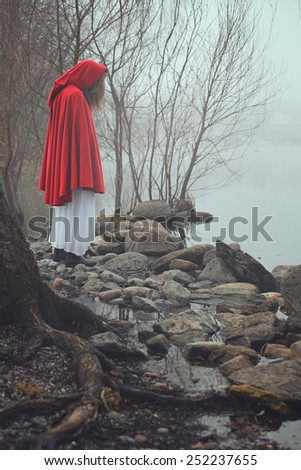Dark and sad portrait of a red hooded woman . Dream and surreal colors - stock photo