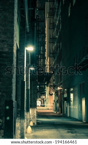 Dark and Spooky Chicago Alley in Greenish Color Grading. Vertical Chicago Alley Photo. - stock photo