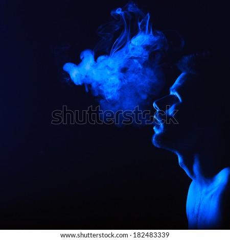 dark and sullen shot of a young man smoking over a black background - stock photo