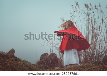 Dark and surreal  portrait of a red hooded woman . Sadness and loneliness conceptual - stock photo