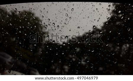 Dark atmosphere rain drops on the other side of the glass. With the coming of the rainy season