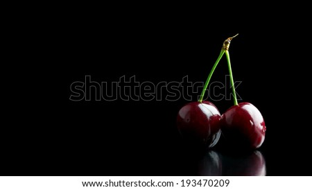 Dark atmospheric image of two ripe red cherries on a joined stalk on a black reflective surface against a dark background with copyspace. - stock photo