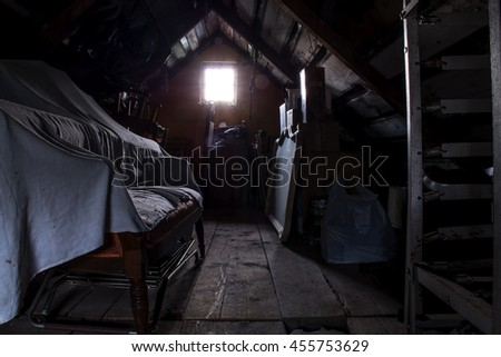 Dark attic with an illuminated window. Includes an old typewriter, a stack of chairs, a covered antique sofa, an old mirror, and rusty old bedframes