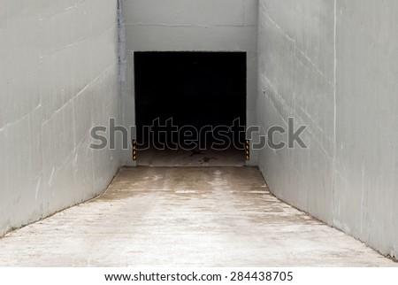 Dark auto garage entrance, stucco walls and ground - stock photo