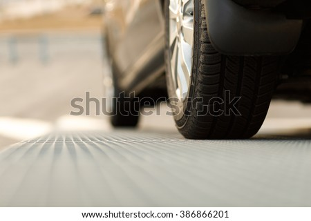 Dark automobile standing on steel floor view from below. Car parking problems, motor show or exhibition, winter season tires, customer purpose loan, vehicles official checkup or examination concept - stock photo