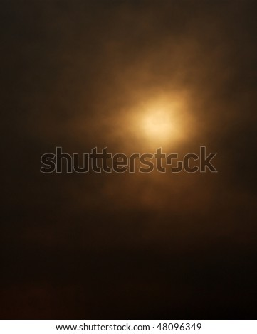 Dark background formed by the sun behind a layer of clouds - stock photo
