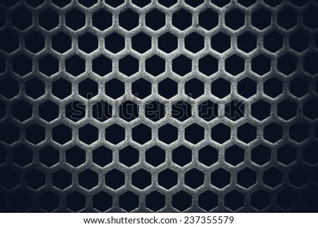 Dark background of a metal lattice with holes - stock photo