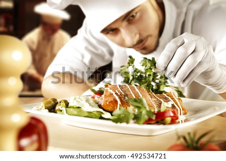 dark background of restaurant kitchen and young men in white clothes making food
