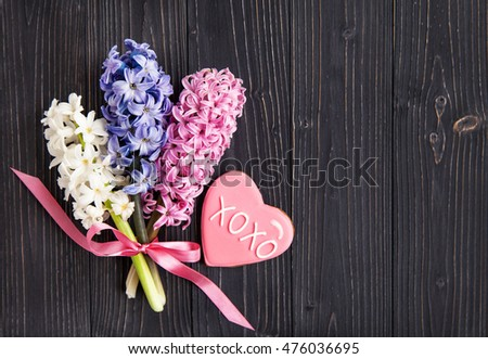 Dark background with fresh flowers hyacinths and biscuits in the shape of a heart