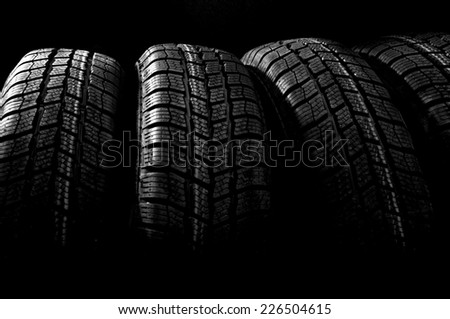 Dark background with winter car tires - stock photo
