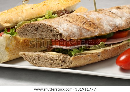 Dark baguette with with ham, vegetables and tomatos