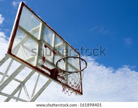Dark basketball hoop and net against blue sky - stock photo
