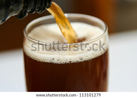 dark beer is pouring into a glass, close up - stock photo