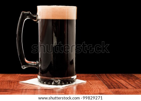 dark beer isolated on a black background served in a chilled mug - stock photo