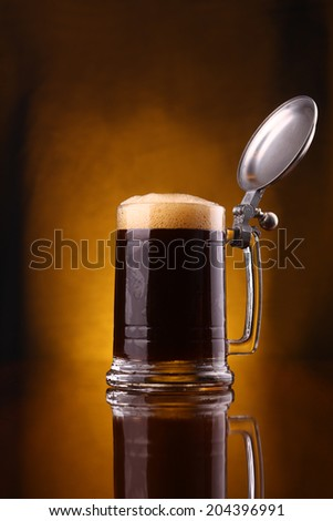 Dark beer pouring into a mug from above over a dark background