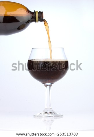 Dark beer pouring into glass - stock photo