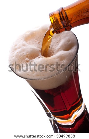 Dark beer pouring into glass on a white background. - stock photo
