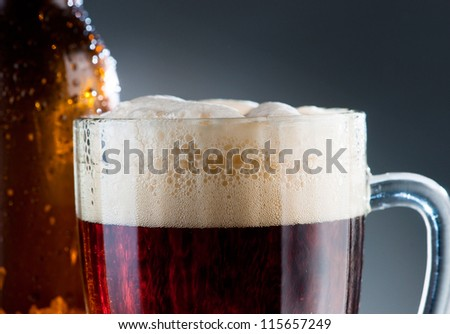 Dark beer with froth in the mug - stock photo