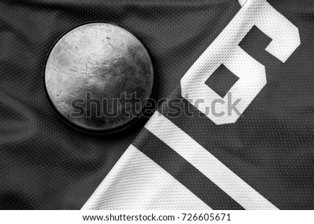 Dark black and white still life puck on a jersey as a winter sport background
