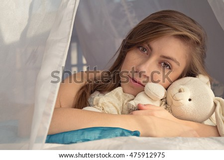 Dark blonde girl lies on bed holding toy rabbit in her hands