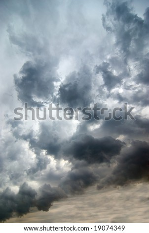 dark blue and orange sky with large clouds - stock photo