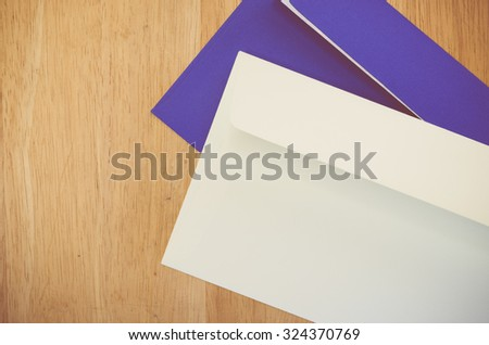 dark blue and white envelope on a natural wood surface with copy space