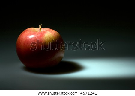 Dark blue background with highlighted red apple. Copyspace provided. - stock photo