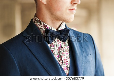 Dark blue bow tie with flowers shirt and suit on men's neck. - stock photo