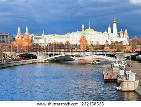 dark blue clouds over illuminated Moscow Kremlin and Moskva River in autumn day - stock photo
