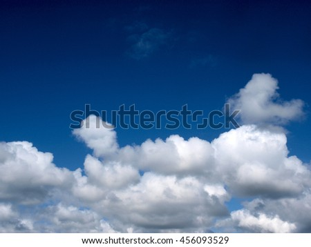 Dark blue color sky with white cumulus clouds for background.        - stock photo