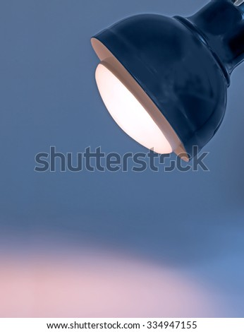 Dark blue metal desk lamp head and large bright light bulb shining a pink spotlight. Slight glow around the lamp. Copyspace. Vertical composition.  - stock photo