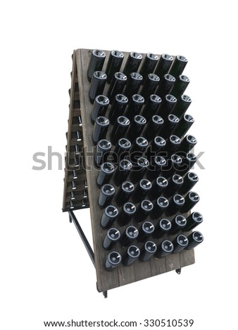 Dark bottles on a wine cellar wooden support isolated over white background