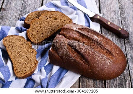 Dark bread with cut pieces on a napkin - stock photo