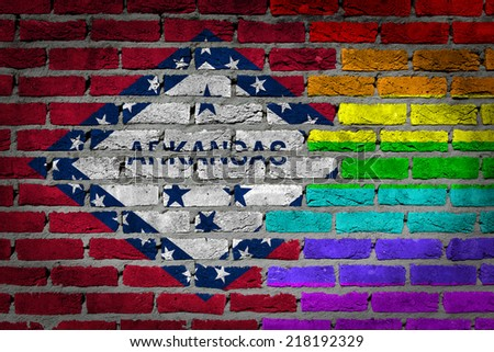 Dark brick wall texture - country flag and rainbow flag painted on wall - Arkansas - stock photo