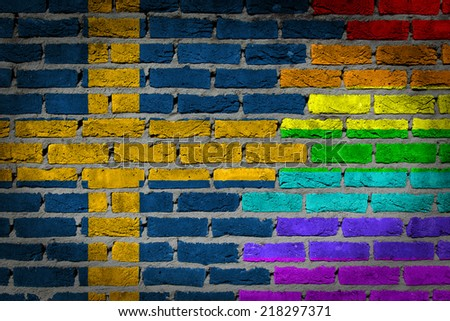 Dark brick wall texture - country flag and rainbow flag painted on wall - Sweden - stock photo