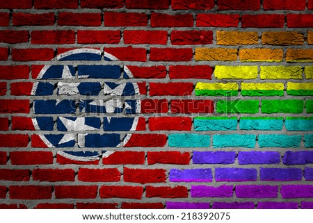 Dark brick wall texture - country flag and rainbow flag painted on wall - Tennessee - stock photo