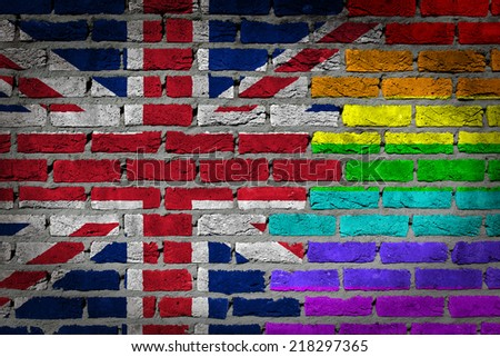 Dark brick wall texture - country flag and rainbow flag painted on wall - United Kingdom - stock photo