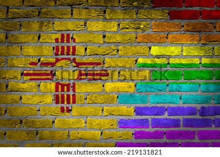 Dark brick wall texture - coutry flag and rainbow flag painted on wall - New Mexico - stock photo