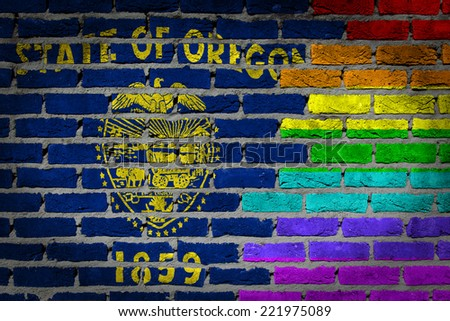 Dark brick wall texture - coutry flag and rainbow flag painted on wall - Oregon - stock photo
