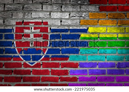 Dark brick wall texture - coutry flag and rainbow flag painted on wall - Slovakia - stock photo